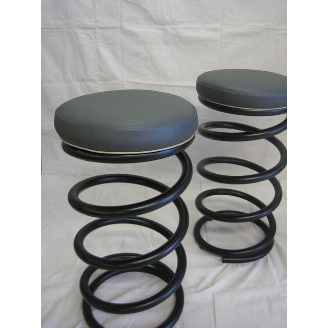 Pair of Heavy duty industrial spring stools, painted black with round tablet style vinyl covered cushions. Dark gray vinyl...