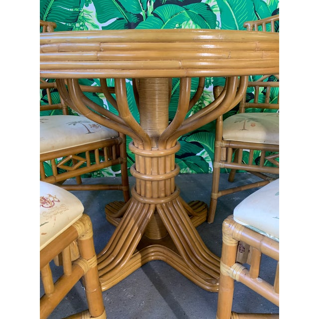 Vintage rattan dining set includes table and four chairs. Two arm chairs and two side chairs. Chinoiserie style design on...