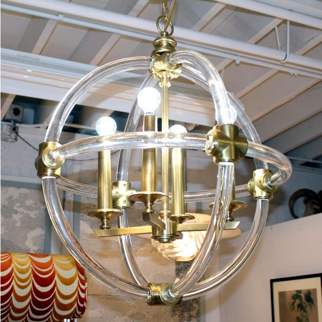 Round, 4 lights, with solid curved clear acrylic rod(s) that reflect light. With brass accents.