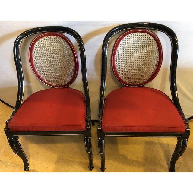 Pair of ebony and red Hollywood Regency style swan head arm or office chairs. Each of these finely constructed chairs have...