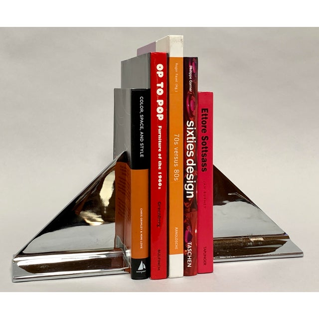 Set of sleek, modern and weighty chromed metal bookends with a slim triangular form set perpendicularly on a rectangular...