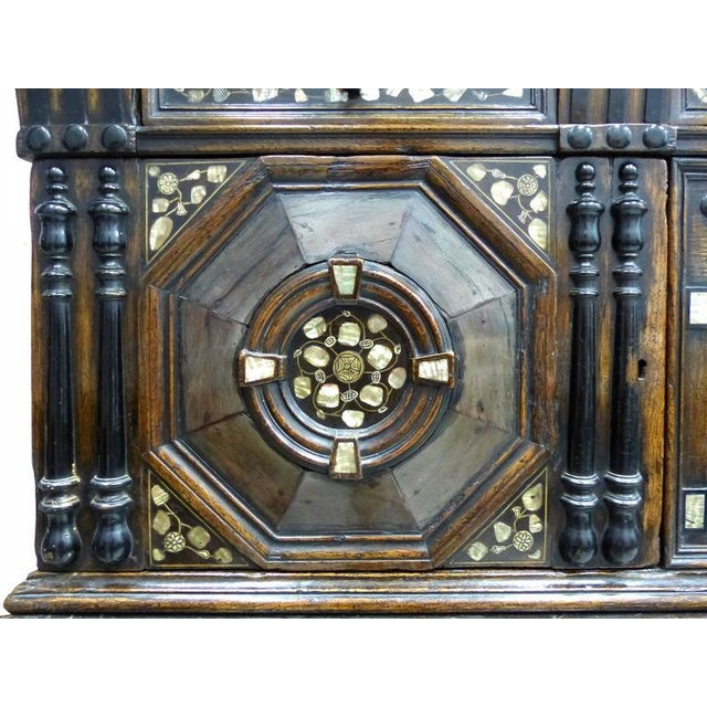 This is a Charles II oak chest on chest press with an overhanging cornice and a frieze drawer. Below are two octagon...