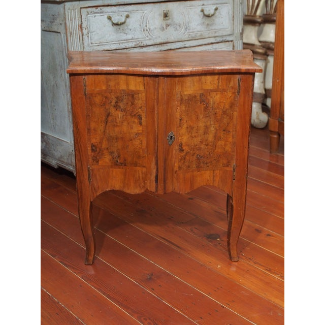 An 18th century Louis XV stye two door veneered cabinet, the shaped case with a conforming top, and scalloped apron, all...