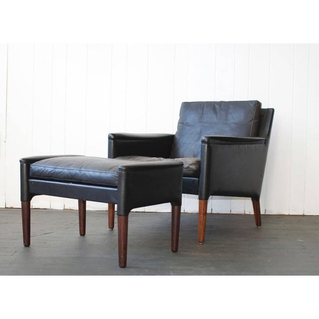 Kurt Østervig leather lounge chair and ottoman with rosewood legs. Down filled seat cushion, Denmark. Chair measures 29.5...