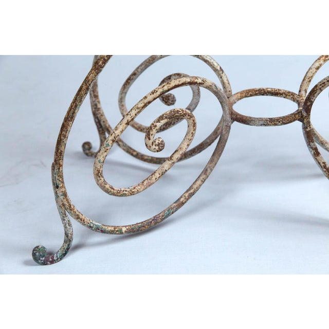 Iron bistro table, France, circa 1910. Curved iron base with glass top. Original painted surface.