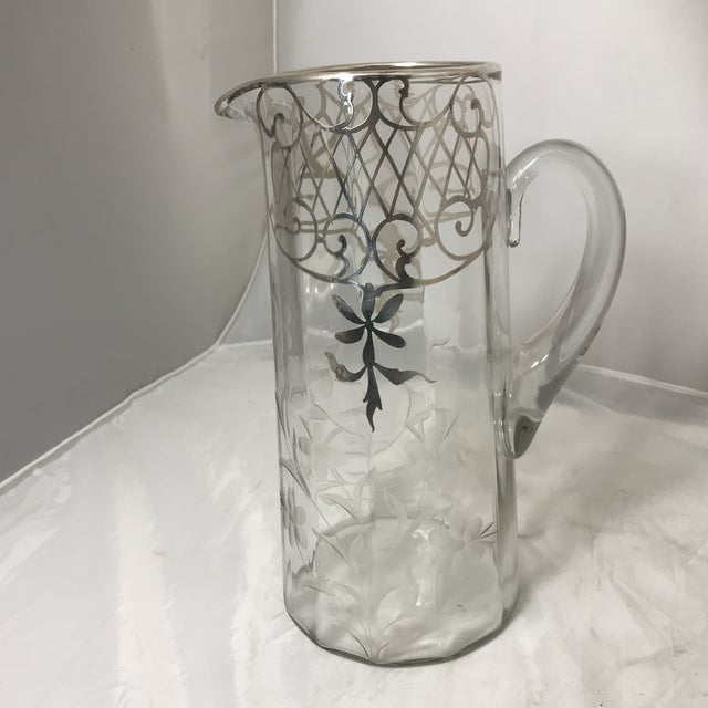 An etched, silver overlay glass set comprising of: a water pitcher, and 6 water glasses. Each are embellished with ridged,...