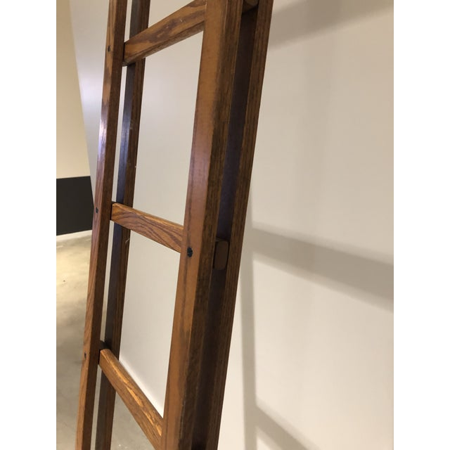 """Folding oak stick ladder circa 1930. When collapsed, measurements are 125.5""""H x 14.5""""W x 2.5""""D. When unfolded..."""