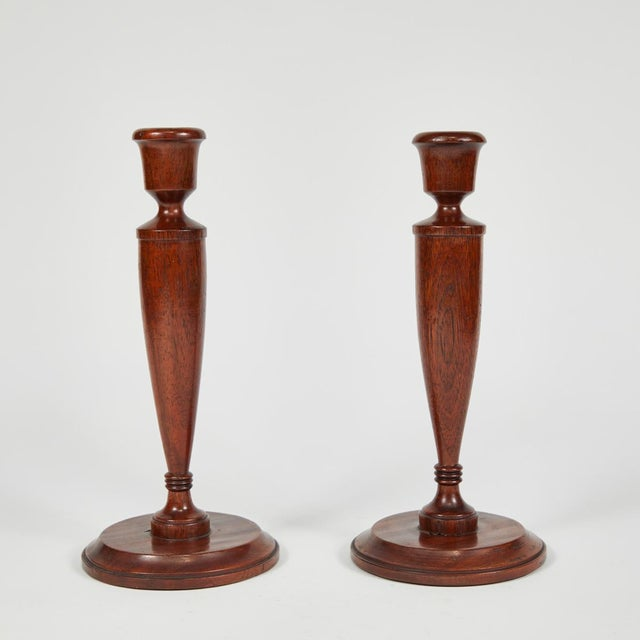 A pair of turned candlesticks in mahogany.