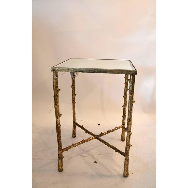 This vintage side table features a gilded faux bamboo frame. The piece was made in the '80s.