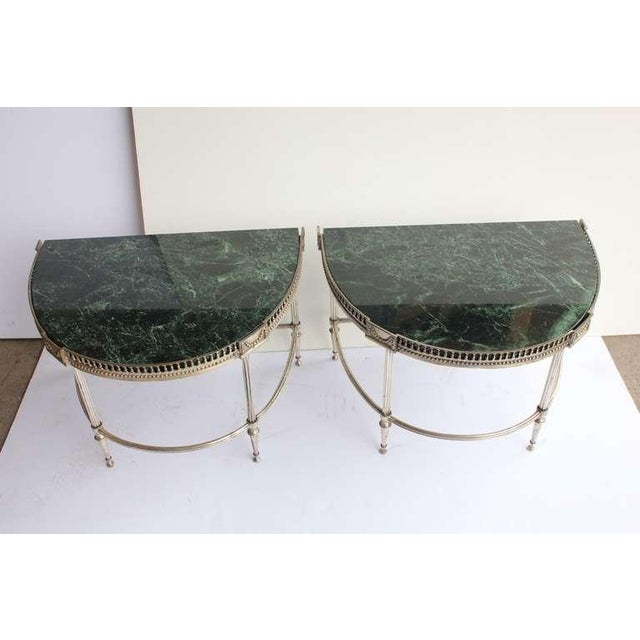 Elegant pair of Jansen style demilune tables with marble tops.