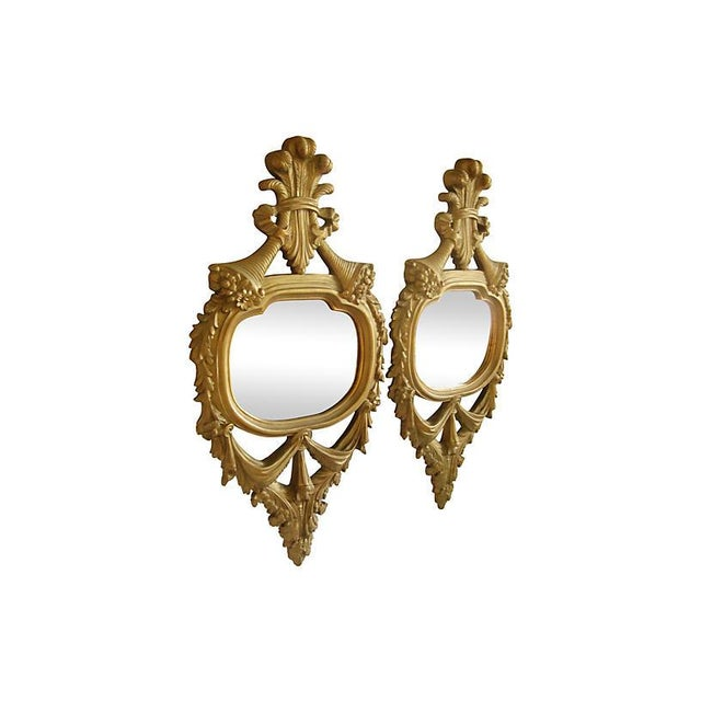 Pair of antique French carved giltwood mirrors. Dramatic swags and soft scrolls culminate into a distinctive acanthus leaf...