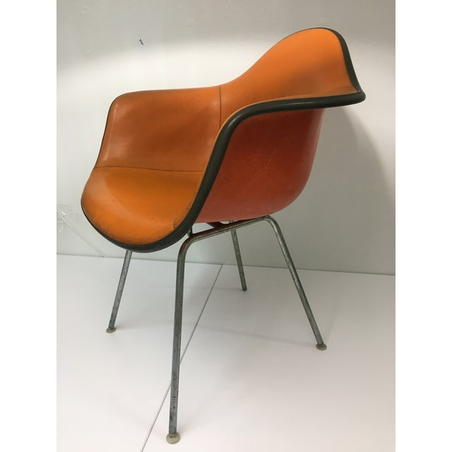 Authentic from the mid-century era, this chair features burnt orange stitched leather upholstery over molded fiberglass...