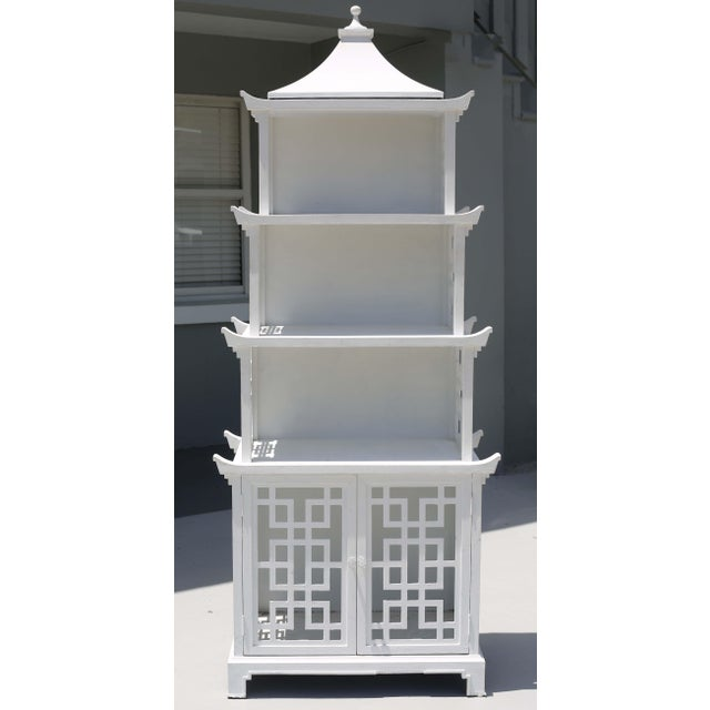 A vintage, white-painted wood bookcase or etagere, with a tiered pagoda form and fretwork design on the front and sides....
