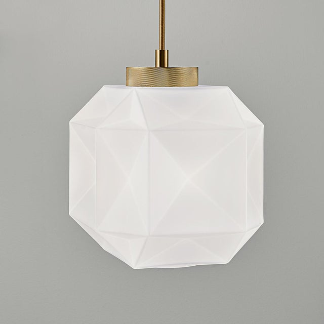 Matt opal hand blown glass pendant in a geometrical pattern. Brushed brass metalwork and a gold soilk covered cable....