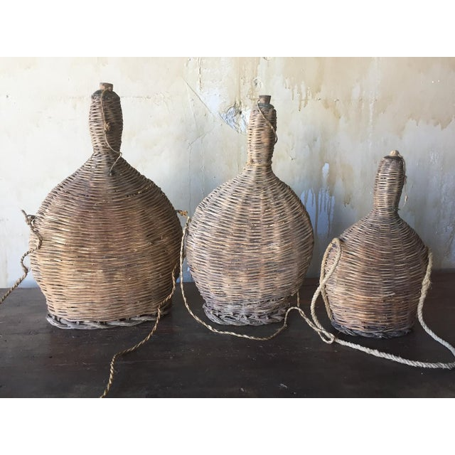 This set of 3 portable Italian antique hand blown glass and reed woven flasks are decorative today but were once used out...