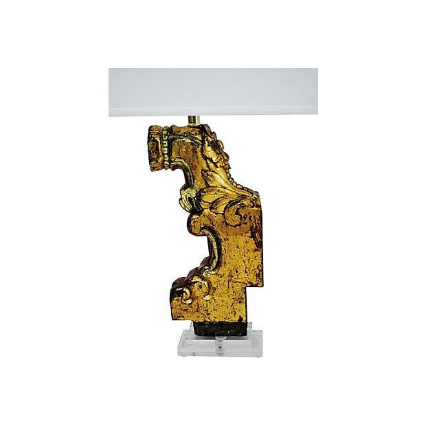Pair of table lamps made with antique architectural wood pieces that have a hand-painted gold finish. The lamps are...