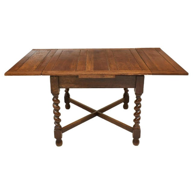 English oak pub table made in the early 20th c. This table consists of a plank top, with draw leaves on either side. The...