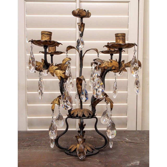 A pair of four light candelabra of hand forged iron decorated with gilded leaves. Each fixture is topped with a simple...