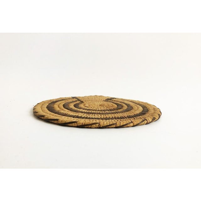 A vintage native american coil wall hanging woven with natural fiber in a two tone color scheme. Quite possibly by the...