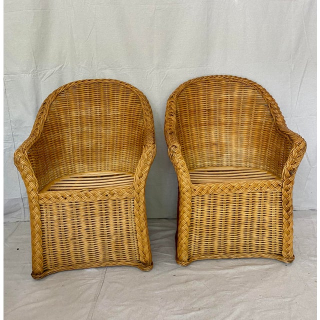 Vintage pair of woven wicker chairs with braided wicker trim. Would be great as captain's chairs at a dining table, or as...
