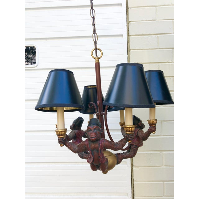 Vintage red, gold and black monkey chandelier. Each monkey wears a hat and vest and holds a light in each hand, to...