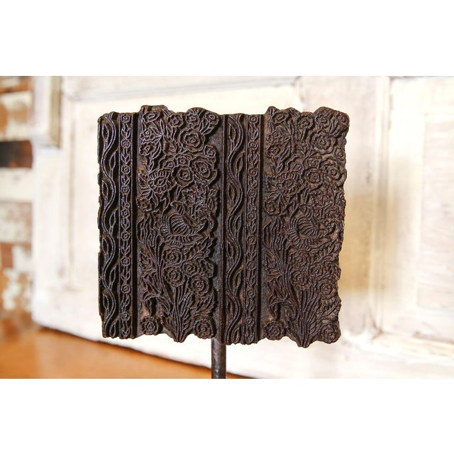 Vintage wood print block hand carved with foliage designs on an metal stand.