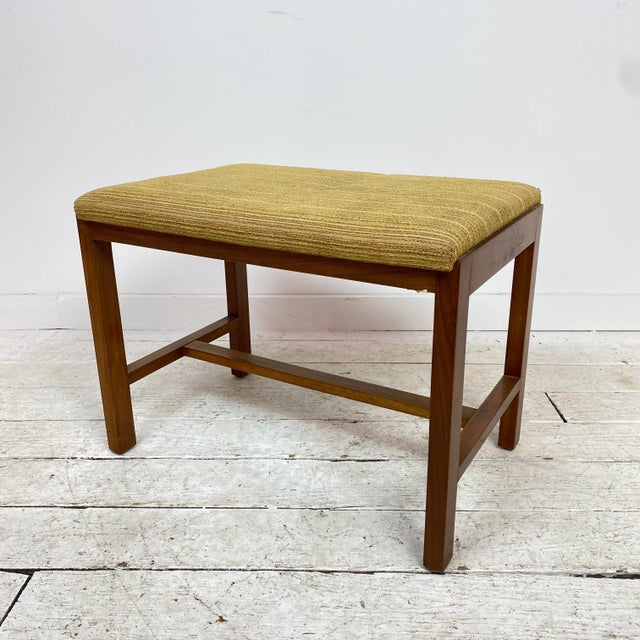 Mid-century modern stool by Dunbar. It has a classic clean design and is currently upholstered in a textured light green...