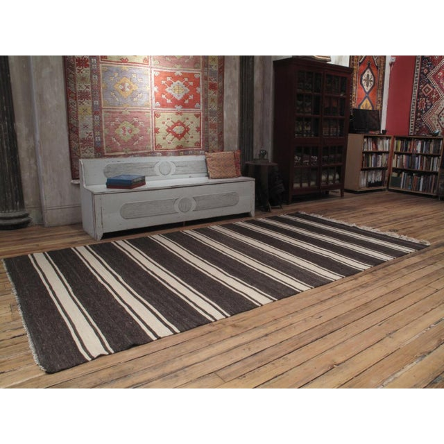 A tribal Kilim woven with alternating bands of brown and ivory un-dyed wool with great tonal variations. A very sturdy...