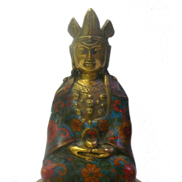 This is a restored Buddha statue made of metal with golden gilt color. The dressing of the Buddha is decorated with blue...