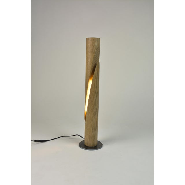 Ash desk lamp cleaved into a sliced from a single ash dowel into a mirrored-configuration. An LED lighting element rated...