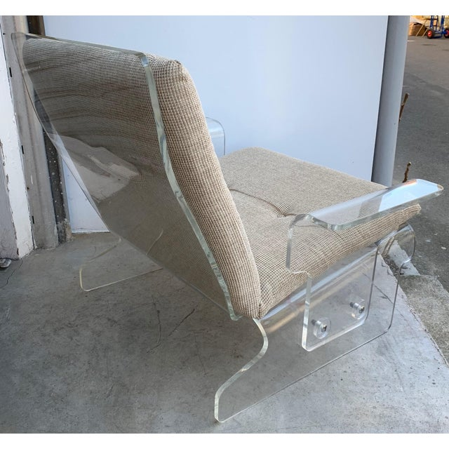 Pair of Lucite armchairs model sleigh system by the German editor Baumann. Nice brass details on side. The full living...