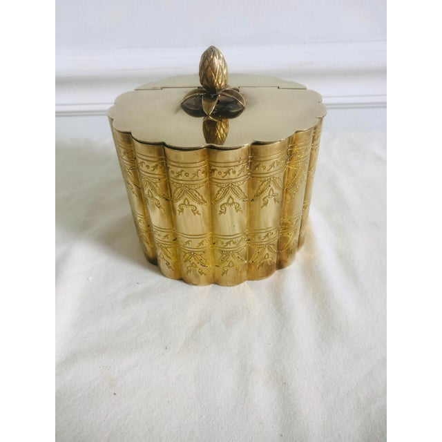 A pineapple finial adorns this nice engraved brass trinket box with hinged lid. Stamped solid brass, made in India.
