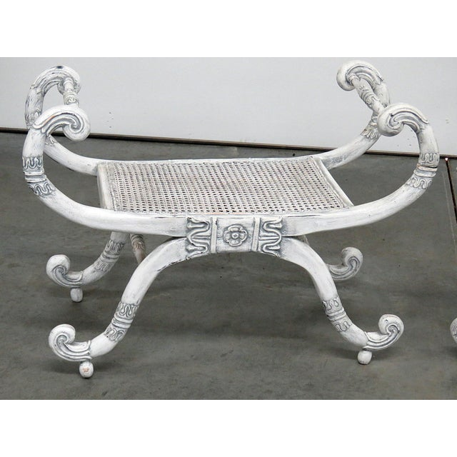 Pair of distressed painted curule benches with caned seats. Circa Early 20th Century.