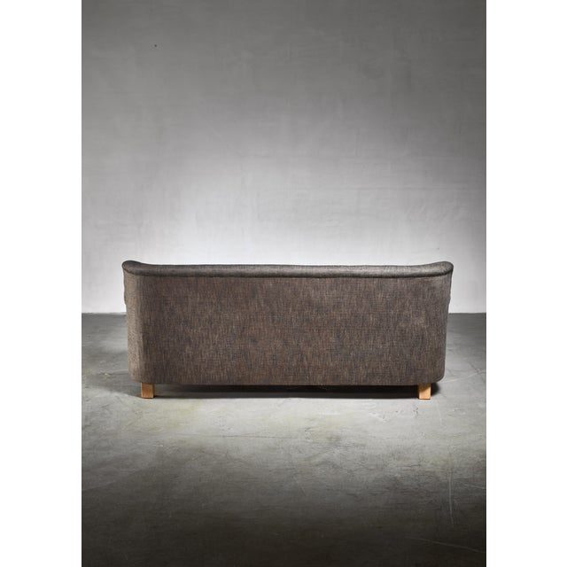 A model A577 three seater sofa by Artek, Finland. This large and comfortable sofa has a brown/black fabric upholstery from...