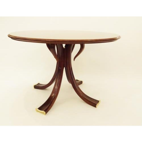 Rare and important round center table featuring a body in stained Cherry with an elegantly designed base. The base is...