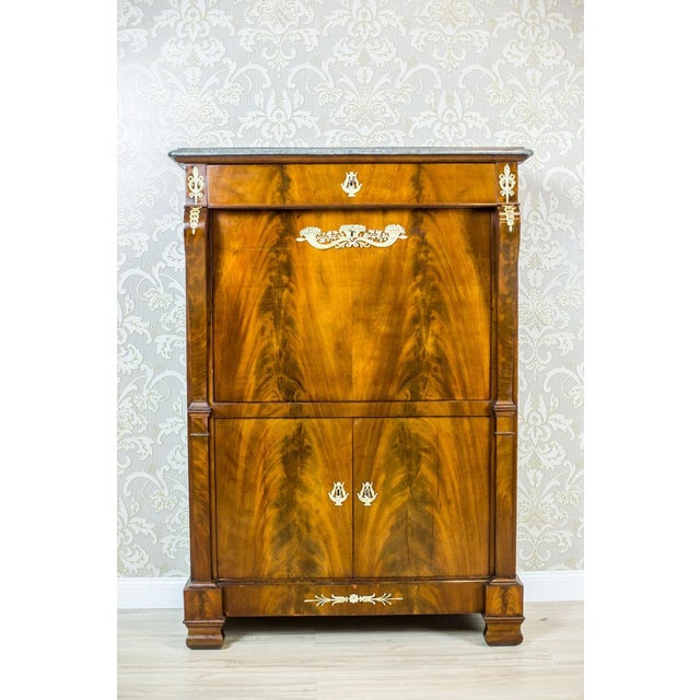 We present you an antique piece of furniture covered with mahogany veneer with beautiful grain. It is topped with a green...