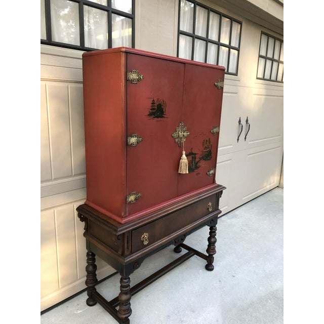 Beautiful antique cabinet in red with painted scenes and ornate brass hardware. May be a wedding cabinet but I'm not sure....