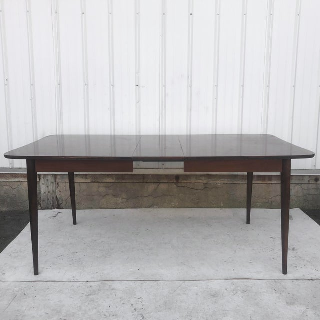This mid-century dining table features clean modern lines in a vintage dark walnut finish. The faux wood formica style...