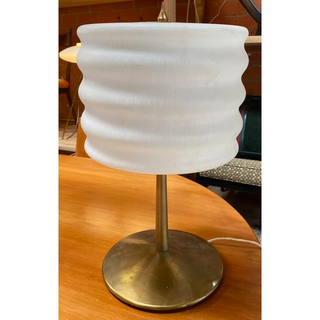 A brass and Glass table lamp designed and manufactured by Gaetano Sciolari, name impressed on the bottom. Brass and glass...