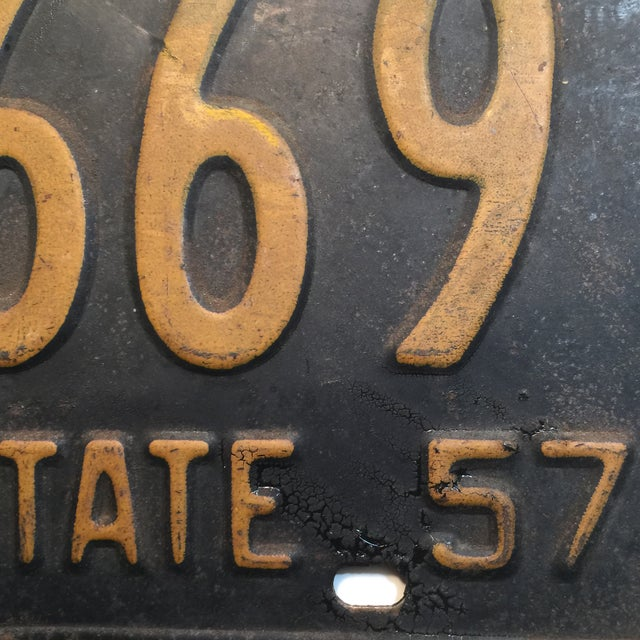 As to be expected, this license plate has some dents along the edges, rust evident. New York Empire State, 1957.