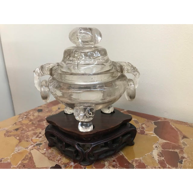 A hand carved Chinese rock crystal incense burner from the late 19th to early 20th century. On a carved wooden stand.