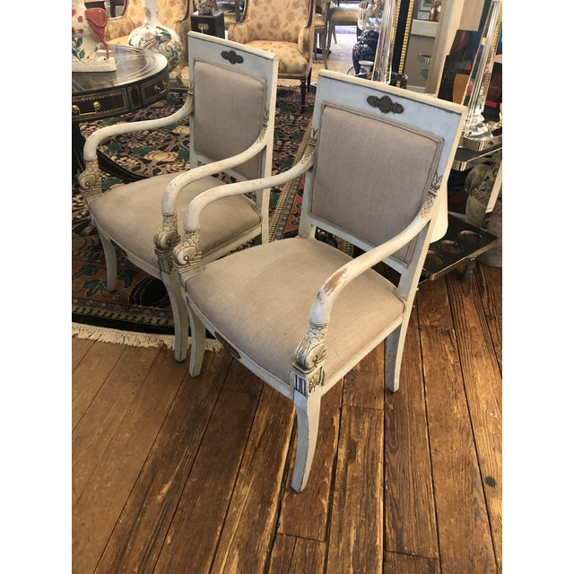 A pair of armchairs so pretty they will turn heads, painted the palest blue with cream detailing and areas of underpaint...