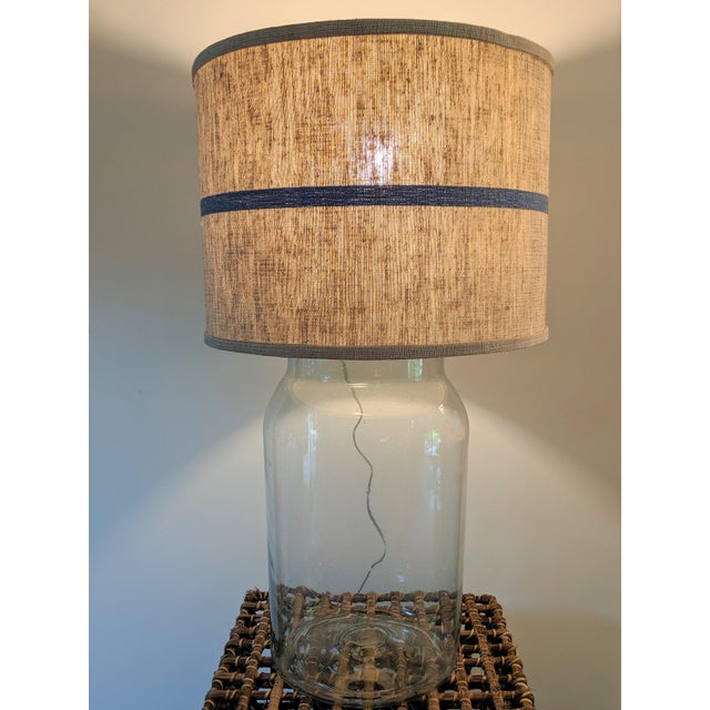 Blown seeded glass lamp base with a natural woven fabric shade with a blue stripe woven into the fabric. Very much has a...