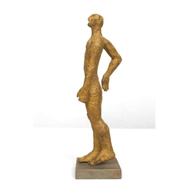 2000s American abstract gold patina bronze sculpture of a standing figure with one arm bent and the other straight on a...