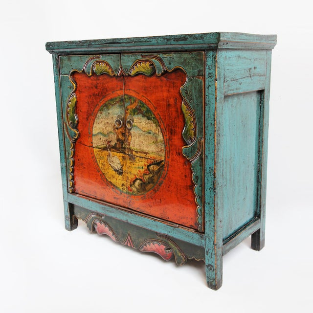 Beautiful hand painted and lacquered storage cabinet from Mongolia. This piece features a circular center design painted...