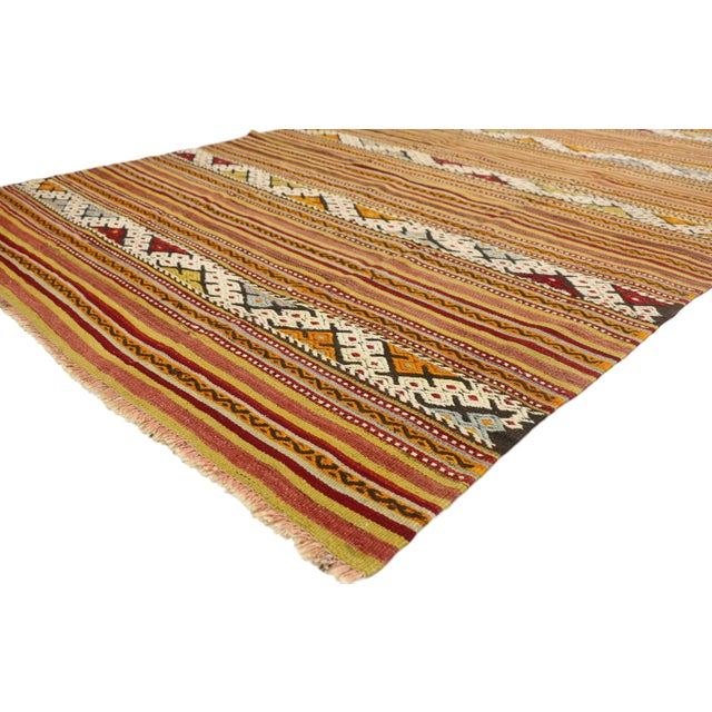 This hand-woven wool vintage Turkish Kilim rug features a series of alternating stripes and bands with geometric Turkish...
