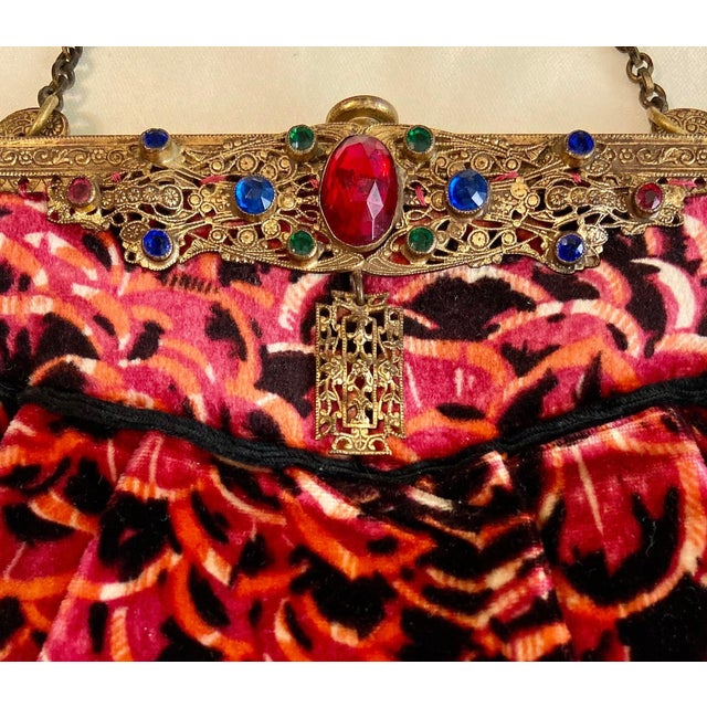 1920s purse in bright pink, orange and black patterned velvet with an ornate brass frame. The frame is bezel set with...
