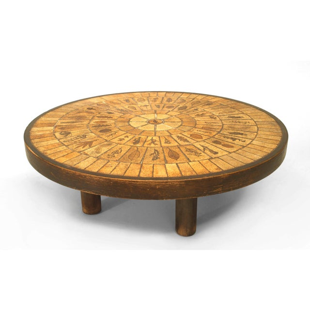 French 1960s round coffee table with a round inset beige ceramic tile top having a sunburst design and decorated with...
