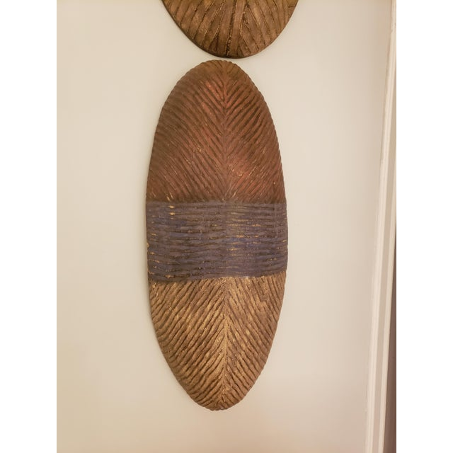 Dissimilar pair of decorative African shields. Shields may be sold separately. Measurements for larger shield are H 25.5,...