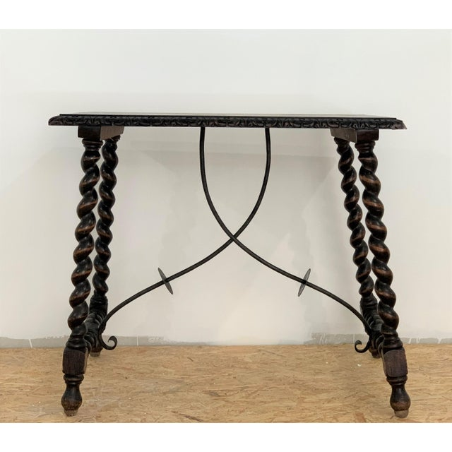 Carved wooden table with smooth and rectangular upper board, which has two iron fasteners decorated with discs and curves,...
